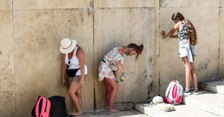 Touristinnen kühlen sich am Trevi-Brunnen in Rom ab.
