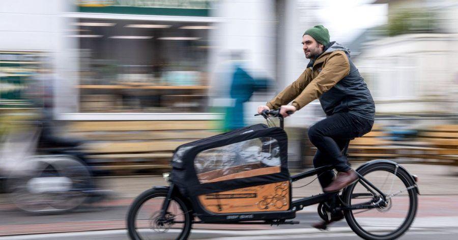 Ernst Schäfer, Mitbegründer des Lastenradverleihs «Rädchen für alles», fährt auf einem Lastenrad durch die Innenstadt.