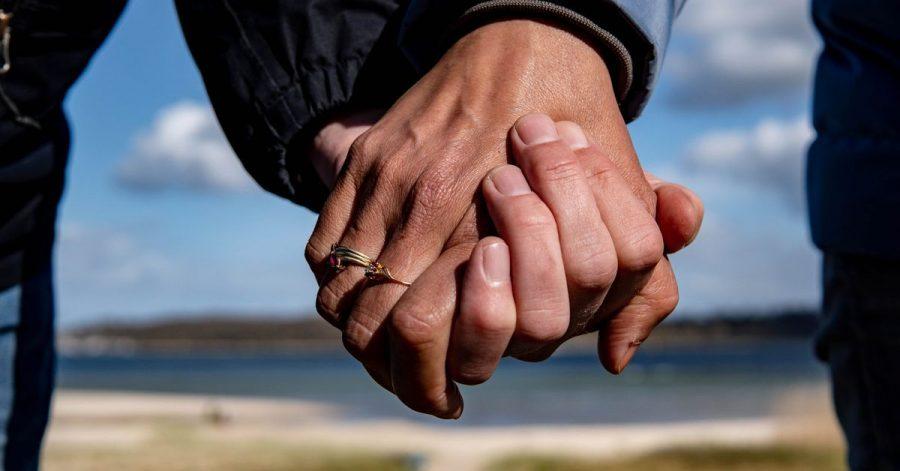 Eine Frau und ein Mann halten sich bei einem Strandspaziergang an den Händen.