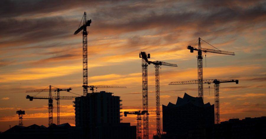 Die Kräne verschiedener Baustellen in der Hafencity zeichnen sich im Sonnenuntergang ab.