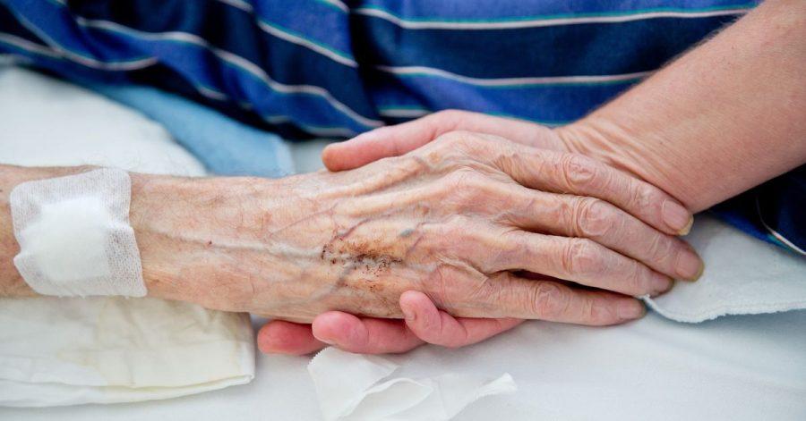 Eine Krankenpflegerin der Onkologie im Klinikum in Nürnberg hält die Hand eines Patienten.