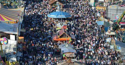 Zahlreiche Menschen gehen bei Sonnenschein über das Oktoberfest-Gelände. In der Pandemie scheint ein solches Massen-Fest kaum denkbar.
