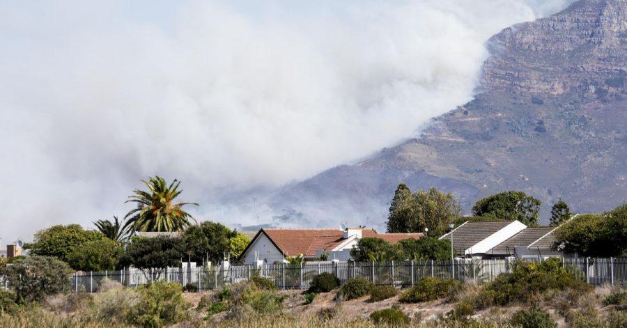 Weißer dichter Rauch steigt über dem Tafelberg auf.