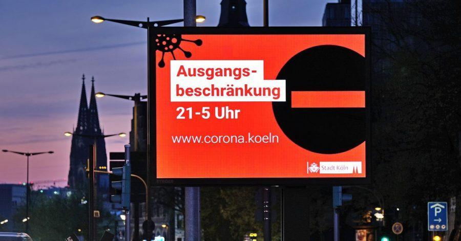 Auf einer Anzeigetafel in Köln wird auf die Ausgangsbeschränkung hingewiesen.