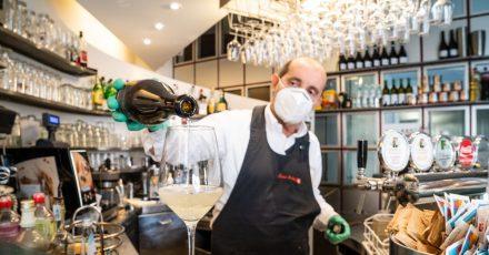 Ein Barmann mit Atemschutzmaske schenkt in Bozen ein Glas Wein ein. (Archivbild)