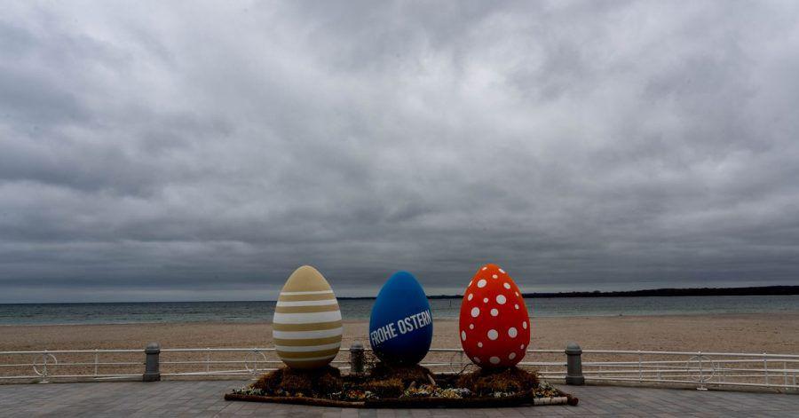 Bunt bemalte überdimensionale Ostereier stehen am wolkenverhangenen Strand von Travemünde.