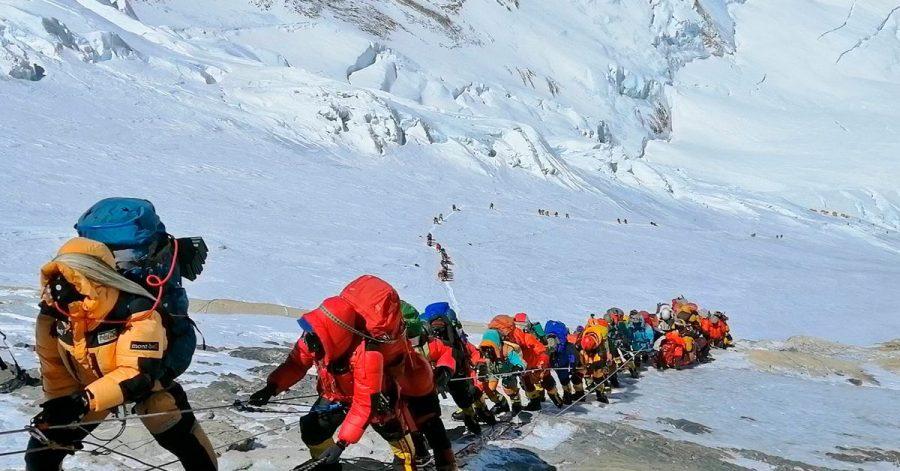 In einer langer Schlange klettern Bergsteiger auf einem Pfad knapp unterhalb von Lager vier.