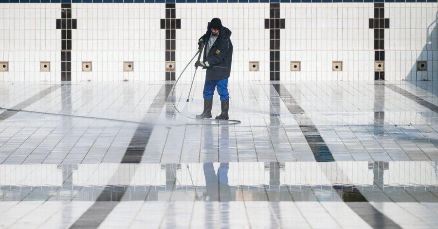 Ein Mitarbeiter reinigt ein Becken im Inselbad Untertürkheim in Stuttgart.