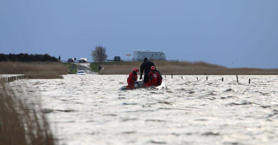 Rettungskräfte im Meer vor Ostfriesland, die von der Flut überraschten Ausflüglern helfen.