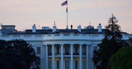 Die Flagge der USA weht bei Sonnenaufgang über dem Weißen Haus.