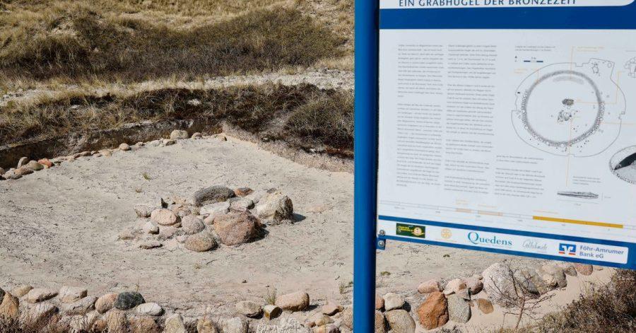 Ein Grabhügel aus der Bronzezeit ist als Denkmal in den Dünen am Strand zu sehen.