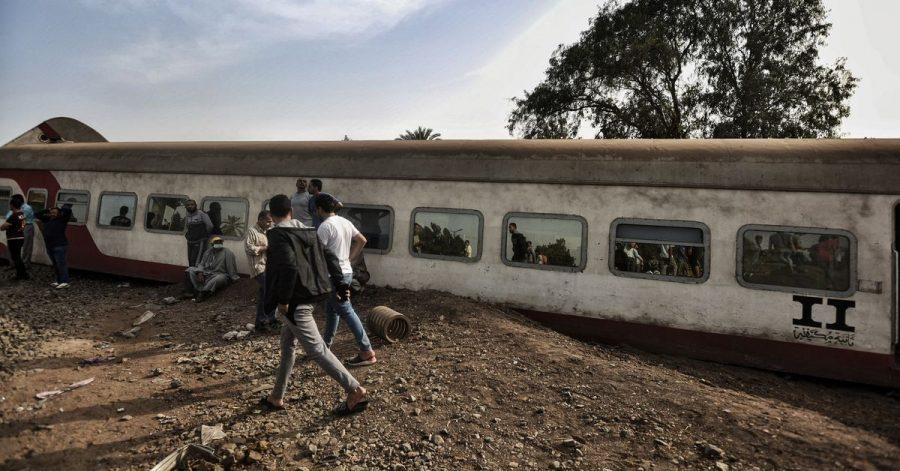 Menschen gehen an einem entgleisten Waggon in der Provinz Kaljubia vorbei.