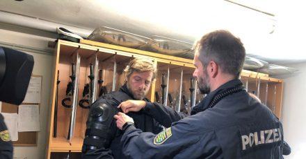 Der Schauspieler Henning Baum (l) zieht eine Schützausrüstung an.