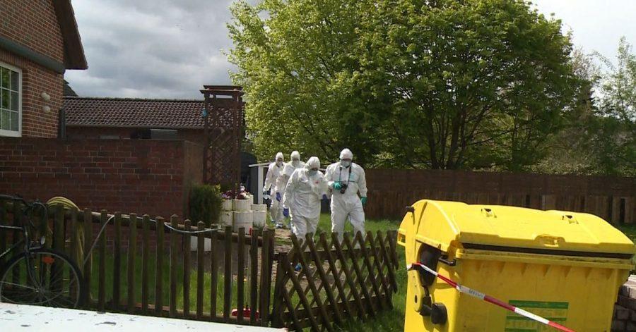 Mitarbeiter der Spurensicherung gehen durch den Garten bei einem Wohnhaus.