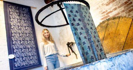 Blaudruckerin Sabrina Schuhmacher zieht den gefärbten Leinenstoff aus der sogenannten Küpe, einem Bottich mit blauer Indigo-Lösung, heraus.