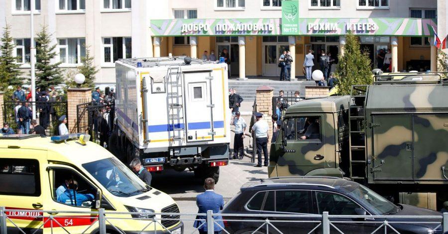 Ein Krankenwagen und Polizeifahrzeuge stehen nach einem Angriff mit Schusswaffen vor einer russischen Schule in Kasan.