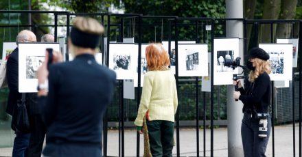 Spaziergänger schauen sich die Outdoor-Fotoausstellung im Rahmen der Ruhrfestspiele am Festspielhaus an.