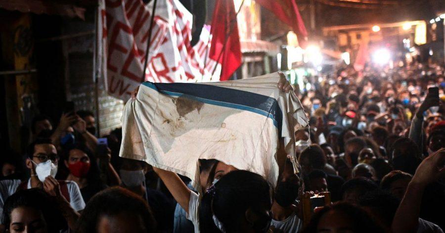 Eine Frau hebt eine Schuluniform mit einem Blutfleck hoch während eines Protests am Tag nach einem tödlichen Polizeieinsatz in der Favela Jacarezinho.