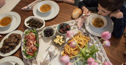 Kinder und Eltern nehmen während des heiligen Fastenmonats Ramadan ein gemeinsames Fastenbrechen-Essen in ihrer Wohnung ein.