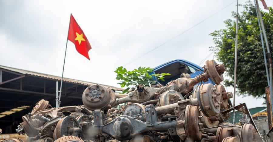 Die Flagge Vietnams weht in Te Lo über einem Haufen rostiger Autoachsen, dahinter steht eine leere LKW-Kabine.