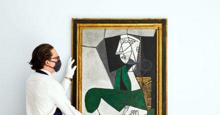 Ein Mitarbeiter von Sotheby's hängt das Gemälde «Femme assise en costume» von Pablo Picasso (gemalt 1953) auf.