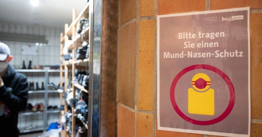 """In der Kleiderkammer der Berliner Stadtmission hängt ein Plakat mit der Aufschrift """"Bitte tragen Sie einen Mund-Nasen-Schutz""""."""
