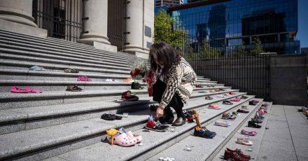 Eine Angehörige einer indigenen Volksgruppe legt eine Rose auf eines von 215 Paar Kinderschuhen auf den Stufen der Vancouver Art Gallery.