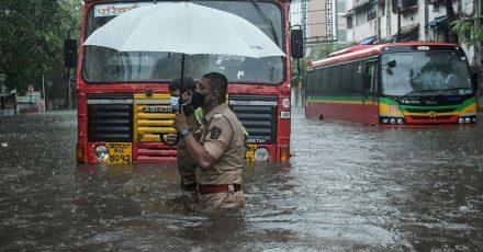 Ein Polizist hilft in Mumbai einem Fahrer eines öffentlichen Verkehrsmittels, eine überschwemmte Straße zu überqueren.