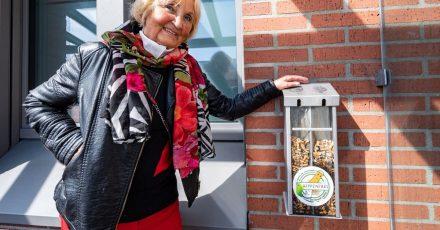 """Karin Meixner-Nentwig von dem Verein """"Amberger Kippenjäger"""" neben einem Sammelbehälter mit Zigarettenkippen."""