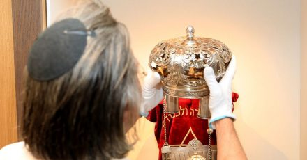 Der Kurator Uri Faber setzt eine Krone auf eine Torarolle mit Mantel im Berend Lehmann Museum in Halberstadt.