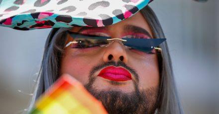 Ein Teilnehmer fächert sich bei der jährlichen Pride Parade Luft mit einem regenbogenfarbenen Fächer zu.