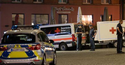 Einsatzfahrzeuge stehen nahe des Tatorts auf dem Barbarossaplatz in der Innenstadt von Würzburg.