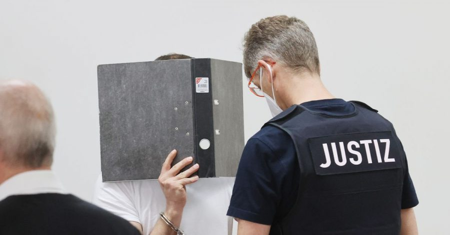 Der Angeklagte (M)wird in Handfesseln in den Verhandlungssaal des Landgerichts Gera geführt.