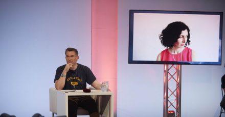 """Ein Bild von Nava Ebrahimi ist auf einem Monitor zu sehen neben einem Mitglied der Jury bei der Lesung am dritten Tag des Wettlesens im Rahmen der """"45. Tage der deutschsprachigen Literatur""""."""