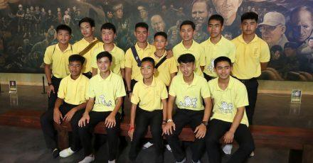 Die 12 Jungs der Fußballmannschaft der «Wildschweine» aus Mae Sai und ihr ehemalige Fußballtrainer Ekkapol Chanthawong (4.v.l, hintere Reihe), die zusammen vor drei Jahren aus der überfluteten Tham-Luang-Höhle gerettet wurden, bei einer Pressekonferenz.