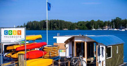 Ein Hausboot und Paddelboote liegen an einem Steg vor dem Schweriner Schloss.