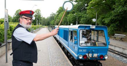 Uwe Schneider, Mitarbeiter der Parkeisenbahn Dresden, hebt am Hauptbahnhof die grüne Kelle zur Abfahrt.