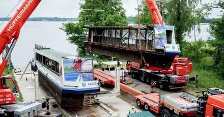 Zwei Mobilkrane heben ein Teilstück des längsseitig zersägten Fahrgastschiffes «MS Oldenburg» am Zwischenahner Meer auf einen Tieflader.