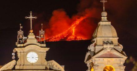 Hinter der Kirche Santa Maria della Guardia in Belpasso bei Catania bricht Lava aus einem Krater des Ätna.