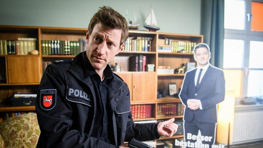 """""""Friesland: Asche zu Asche"""": Henk Cassens (Maxim Mehmet) staunt nicht schlecht, als er einen Pappaufsteller von Habedank im Mohn'schen Bestattungsinstitut findet (cg/spot)"""