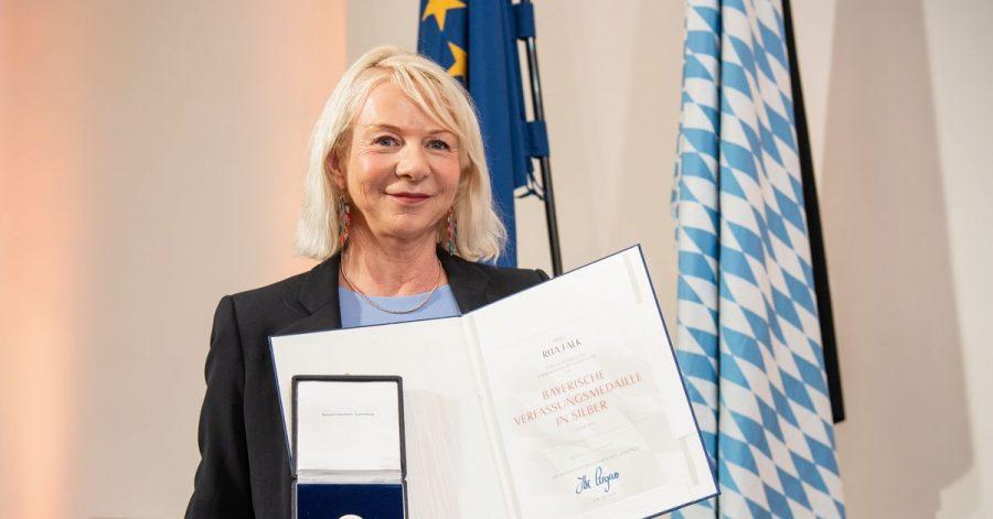 Rita Falk, Autorin, hält bei der Verleihung der Bayerischen Verfassungsmedaille im Landtag ihre Urkunde und Medaille in den Händen.