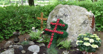 Ein Lothringer Kreuz aus roten Rosen und ein großer Felsbrocken schmücken das Grab des französischen Schauspielers Pierre Brice.