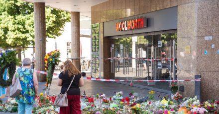 Trauerkerzen und Blumen liegen vor dem Kaufhaus, in dem der Täter Menschen mit einem Messer attackiert hatte.