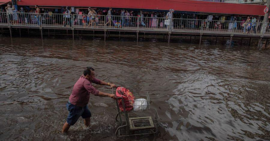 Ein Mann schiebt einen Einkaufswagen durch eine überschwemmte Straße. Die Flüsse rund um die brasilianische Amazonas-Metropole Manaus haben nach starkem Regen Rekordstände erreicht und heftige Überschwemmungen verursacht.