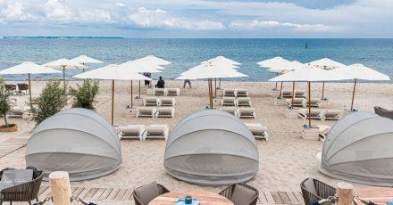 Strandliegen und Sonnenschirme stehen in Timmendorfer-Strand für Badegäste bereit.