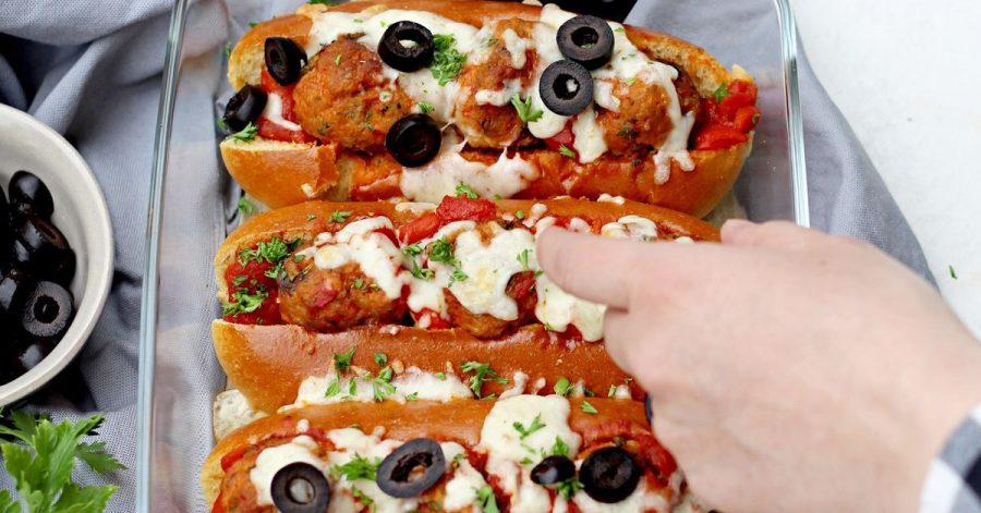 Bevor die Meatball Sandwiches im Ofen für 10 Minuten mit Mozzarella überbacken werden, kommen in jedes Briochebrötchen 3 Hackbällchen und etwas Soße.