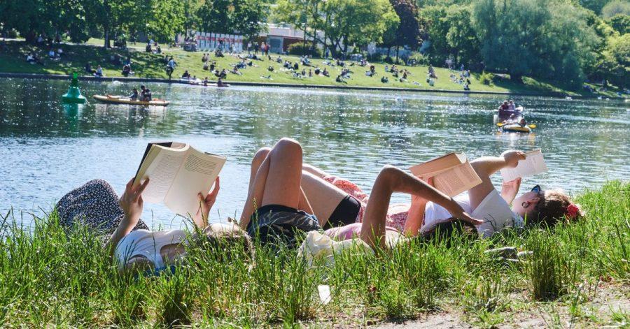 Drei Frauen liegen auf der Wiese am Landwehrkanal in Berlin und lesen Bücher.