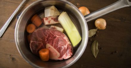 Knochenstücke vom Rind werden über viele Stunden knapp unter dem Siedepunkt ausgekocht. Wer mag, gibt frisches Gemüse dazu.