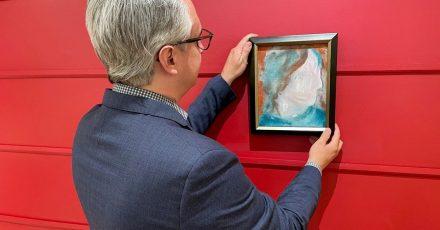 Rob Cowley, Präsident & Senior Spezialist bei Cowley Abbott, hängt ein zufällig in einem Spendenzentrum für Haushaltsgegenstände entdecktes Gemälde von Musik-Legende David Bowie (1947-2016) an die Wand.