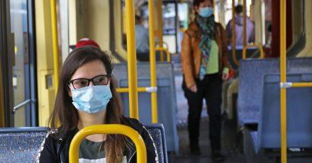 Cathrine sitzt mit einer Schutzmaske in einer Straßenbahn.